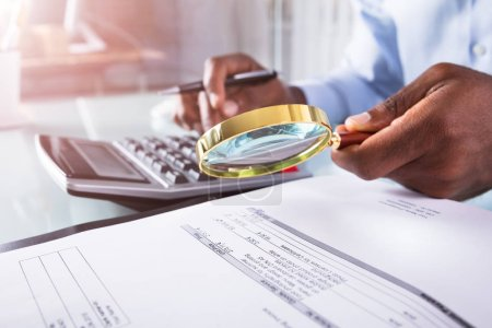 Close-up Of A Businessman Holding Magnifying Glass Over Invoice Using Calculator