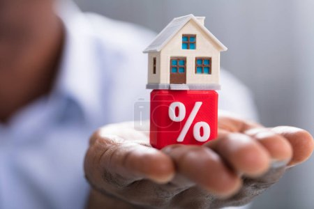 Close-up Of A Person's Hand Holding Miniature House On Red Percentage Block