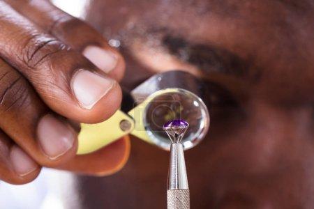 Close-up Of Jeweler Examining Diamond Through Loupe