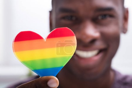 Smiling Man Holding Rainbow Heart In His Hand Against White Background