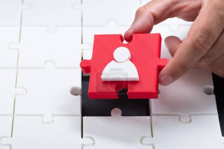 Close-up of a person's hand placing red human figure piece into jigsaw puzzle