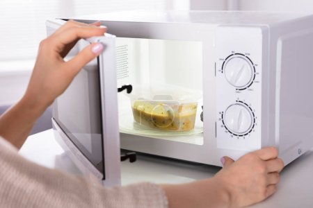 Photo for Close-up Of A Woman's Hand Preparing Food In Microwave Oven - Royalty Free Image