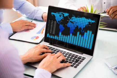 Businessperson Using Laptop With Graph On Screen