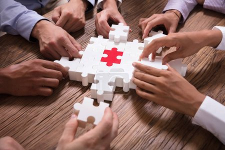 Elevated View Of Businesspeople Solving Jigsaw Puzzle Over Wooden Background