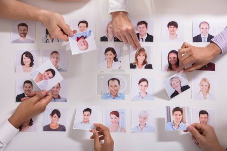 Elevated View Of Businesspeople Selecting Candidate Photo On White Background