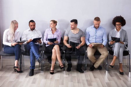 Candidates Sitting In A Row Waiting For Job Interview