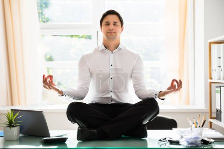 Relaxed young businessman meditating in lotus position on glass desk