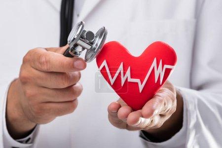 Photo pour Gros plan de la main du médecin examinant la fréquence cardiaque rouge avec stéthoscope - image libre de droit