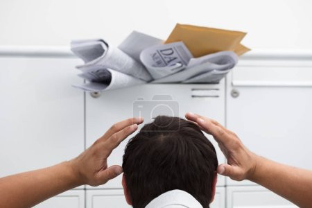 Close-up of man with hand on head in front of overloaded mailbox with junk mail