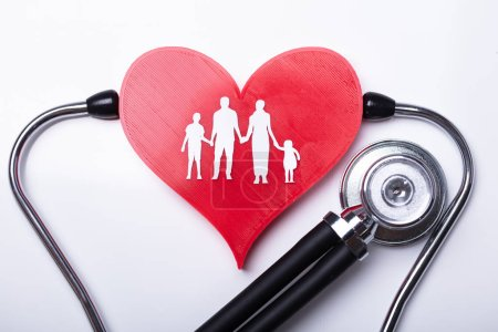 Elevated View Of Stethoscope Examining Red Heart With Family Figures