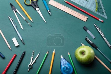 Photo pour Vue à angle élevé de diverses fournitures scolaires sur tableau vert - image libre de droit
