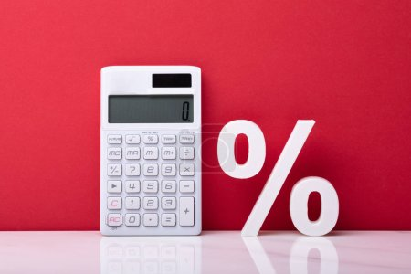 Calculator And White Percentage Symbol Against Red Backdrop