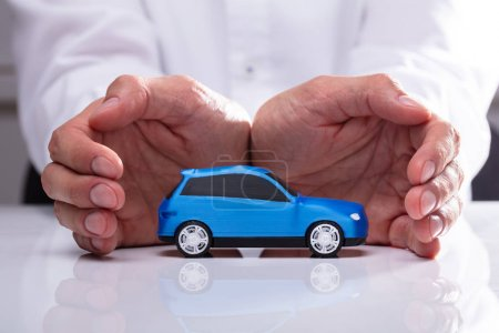 Businessman's Hand Protecting Small Miniature Blue Car