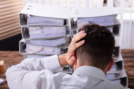 Close-up Of Stressed Businessman With Hand On Head In Front Of Stacked Folders