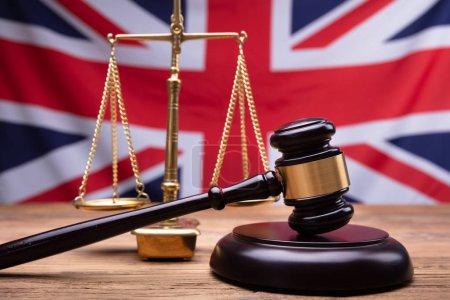 Photo pour Gros plan du juge maillet en bois et échelle de Justice devant drapeau Uk - image libre de droit