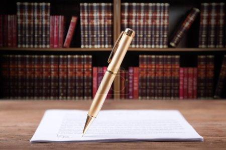 Foto de Pluma de firma de documento en el escritorio en la sala de audiencias - Imagen libre de derechos