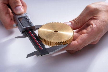 A Person's Hand Measuring Gear's Size With Digital Electronic Vernier Caliper On White Background