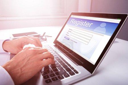 Photo pour La main de l'homme d'affaires remplissant le formulaire d'inscription en ligne sur ordinateur portable - image libre de droit