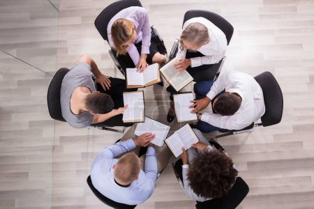 High Angle View Of People Sitting In A Circle Reading Bible