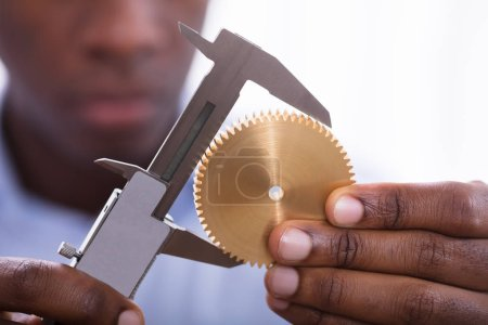 Close-up Of A Person Holding Golden Gear Measuring With Vernier Caliper