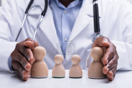 Photo pour Gros plan du docteur stéthoscope protégeant la famille pion en bois avec sa main sur le Bureau - image libre de droit