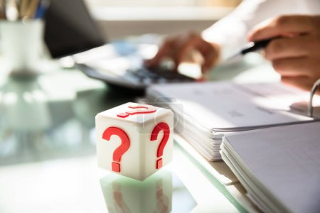Photo pour Bloc cubique avec panneau d'interrogation rouge sur un bureau en verre - image libre de droit