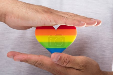 Close-up of a man's hand holding rainbow LGBT heart
