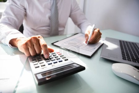 Close-up Of A Businessman's Hand Calculating Invoice With Calculator