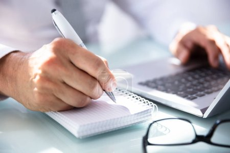 Photo for Close-up Of A Businessman's Hand Writing In Diary Over Desk - Royalty Free Image