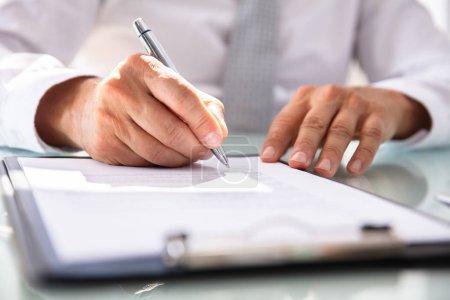 Photo pour Formulaire de contrat de remplissage de main d'homme d'affaires avec le stylo - image libre de droit