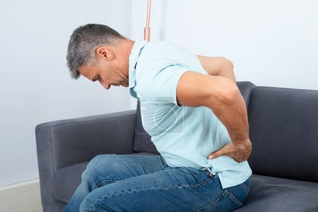 Mature Man Sitting On Sofa Suffering From Back Pain
