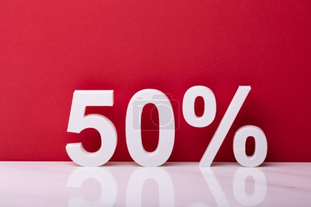 White Fifty Percent Sale Sign In Front Of Red Wall