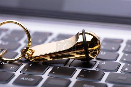 Close-up Of Golden Hotel Keychain On Laptop Keypad