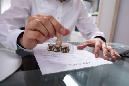 Businessman's Hand Stamping Approved On Contract Paper With Stamper