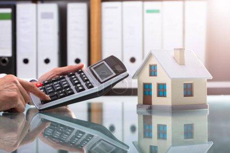 Businessperson's Hand Using Calculator Near House Model Over Reflective Desk