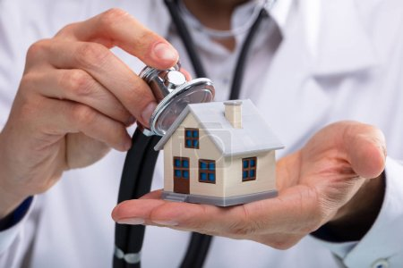 Close-up Of A Doctor's Hand Examining House Model With Stethoscope