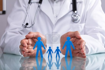 Doctor's Hand Protecting Blue Family Figure Cutout On Reflective Desk