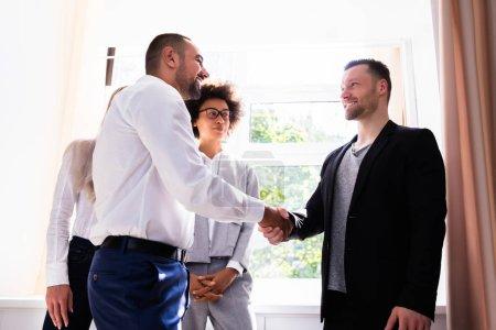 Photo pour Jeune homme d'affaires, serrant la main de son partenaire au lieu de travail - image libre de droit