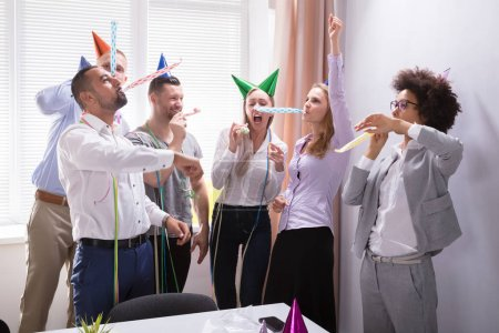 Photo for Group Of Young Businesspeople Celebrating New Year Party In Office - Royalty Free Image