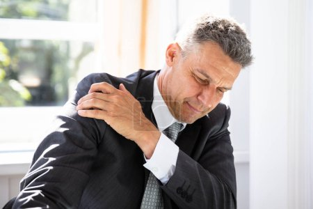 Mature Businessman Suffering From Shoulder Pain At Workplace