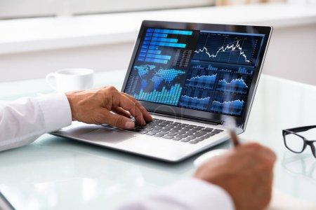 Photo pour Gros plan de main d'un courtier en bourse analyse graphique sur ordinateur portable au bureau - image libre de droit
