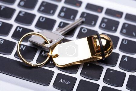 High Angle View Of Hotel Key With Keychain On Laptop Keypad