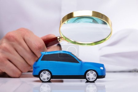 Photo for Businessman's Hand Holding Magnifying Glass Over Small Blue Car - Royalty Free Image