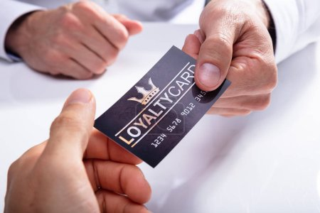 Close-up Of A Businessman's Hand Giving Loyalty Card To His Partner