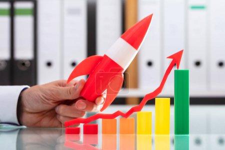 Photo pour Homme d'affaires survolant fusée graphique coloré avec flèche allant vers le haut - image libre de droit