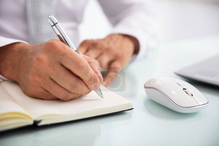 Close-up Of A Businessperson's Hand Writing Schedule In Diary With Pen