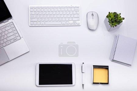 Photo pour Vue élevée de divers appareils électroniques et papeterie sur fond blanc - image libre de droit