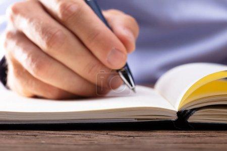 Photo pour Écriture à la main de la personne dans un carnet à l'aide d'un stylo - image libre de droit