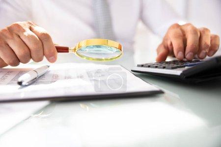 Photo pour Main de l'homme d'affaires en utilisant la calculatrice tout en analysant le rapport financier avec loupe - image libre de droit