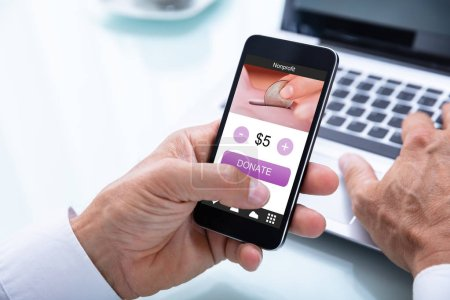 Close-up Of A Businessman's Hand Donating Money Online On Mobile Phone